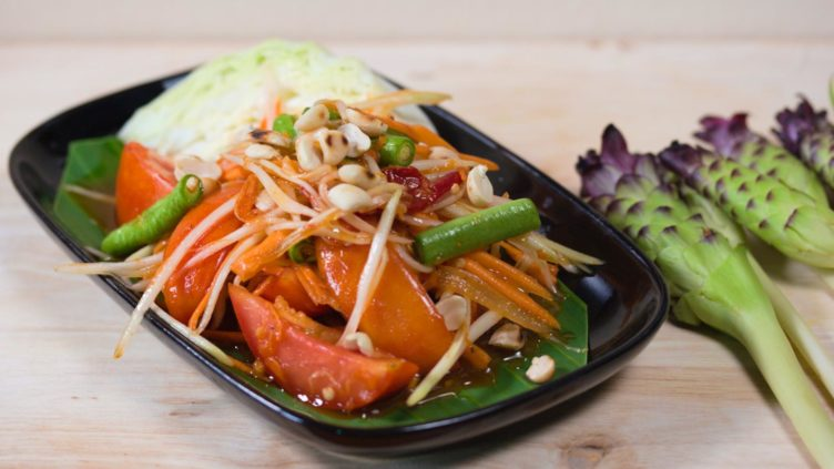 Photo of a plate of som tam thai papaya salad with shredded papaya and tomatoes