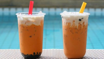 photo of two cups of Thai Iced Milk Tea nd Boba Milk Tea by a swimming pool