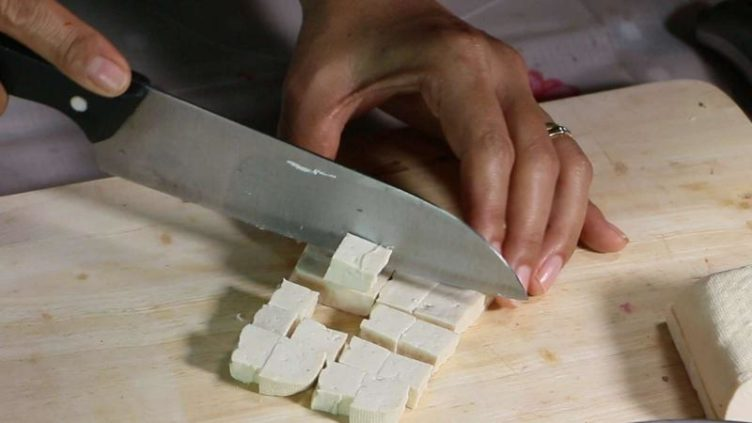Photo showing tofu being cut into cubes for Shrimp Phat Thai