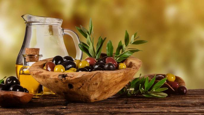 Image of glass bottles filled with quality cooking oil and some olives and herbs to infuse oil in a wooden bowl