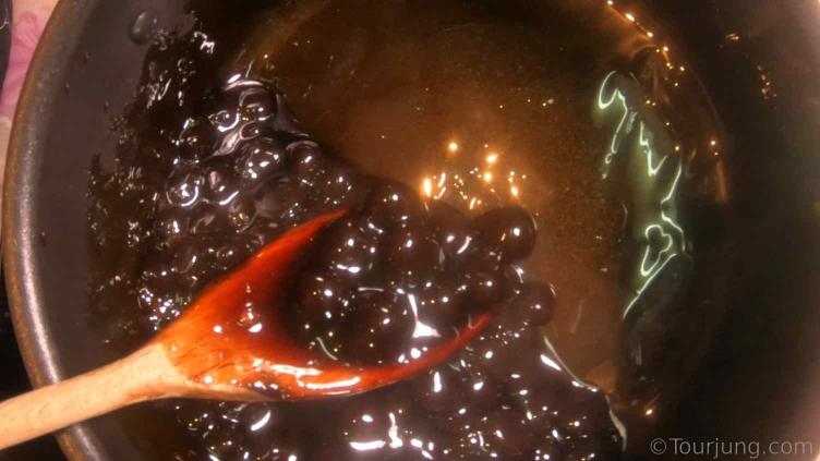 photo of homemade boba pearls being boiled in brown sugar syrup after cooking