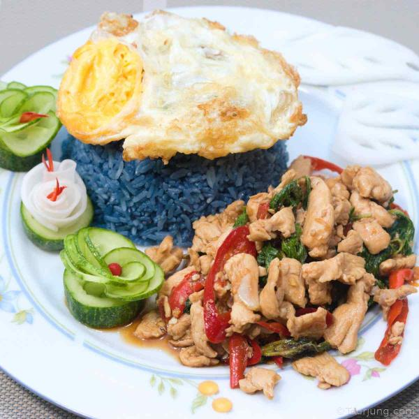 photo of fun Pad Grapow Gai served with blue rice and fried egg