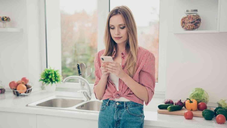 photo of woman using a mobile phone to search for recipe