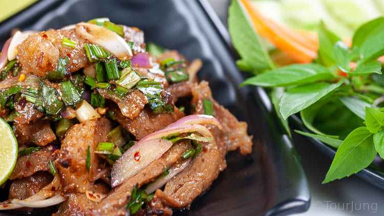 Close up photo of Thai beef salad recipe served on a black plate with side plate of fresh herbs