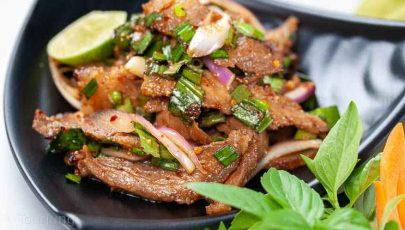 Photo of authentic Thai beef salad recipe served with fresh herbs and sticky rice out of picture