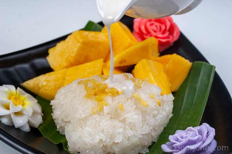 Photo of coconut milk dessert sauce being poured over sticky rice for mango