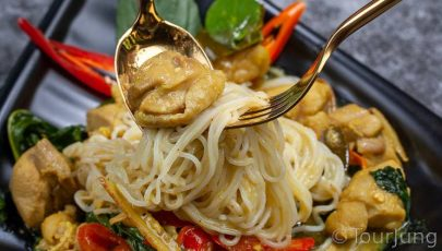 photo of Thai green curry with gold spoon and fork