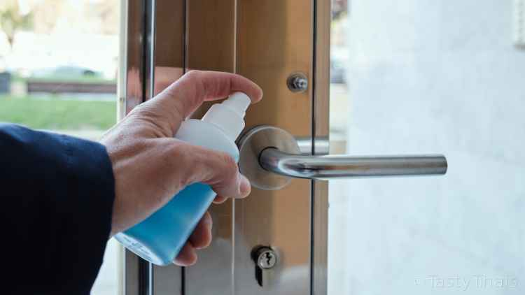 photo of residential door handle being disinfected to rid it of germs after use