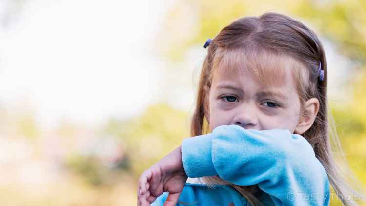 photo of small child coughing and sneezing into her arm