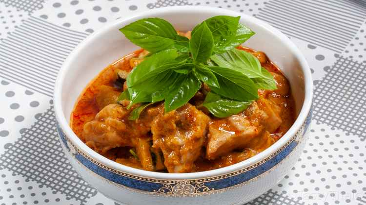 Thai Coconut Chicken Currry with Pumpkin served in a blue and white bowl