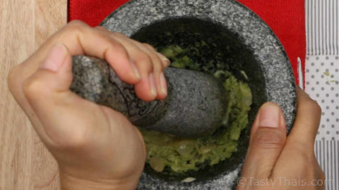Pounding the seafood dipping sauce ingredients in a mortar and pestle